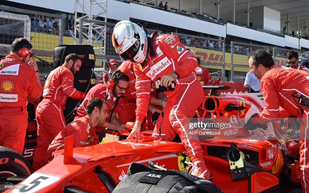 Ferrari's German driver Sebastian Vettel (C) gets out of his car before the start of the Formula One Japanese Grand Prix at Suzuka on October 8, 2017. / AFP PHOTO / Kazuhiro NOGI