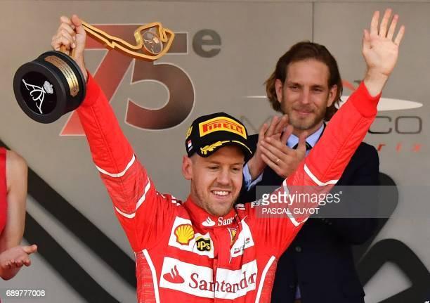 Ferrari's German driver Sebastian Vettel holds his trophy as he celebrates on the podium after winning the Monaco Formula 1 Grand Prix at the Monaco...