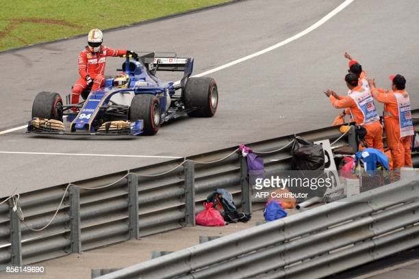 Ferrari's German driver Sebastian Vettel is given a ride by Sauber's German driver Pascal Wehrlein after he crashed past the chequered flag during...