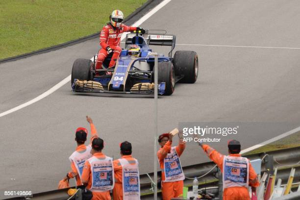 TOPSHOT Ferrari's German driver Sebastian Vettel is given a ride by Sauber's German driver Pascal Wehrlein after he crashed past the chequered flag...