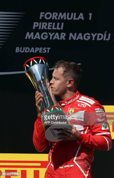 Ferrari's German driver Sebastian Vettel kisses his trophy on the podium after the Hungaroring racing circuit in Budapest on July 30 after winning...