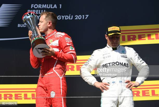 TOPSHOT Ferrari's German driver Sebastian Vettel kisses the trophy after winning the Formula One Hungarian Grand Prix at the Hungaroring racing...