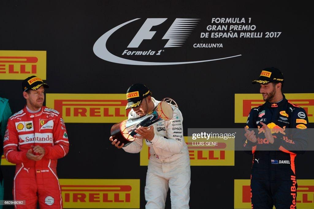 Ferrari's German driver Sebastian Vettel, Mercedes' British driver Lewis Hamilton and Red Bull's Australian driver Daniel Ricciardo celebrate on the podium after the Spanish Formula One Grand Prix on May 14, 2017 at the Circuit de Catalunya in Montmelo on the outskirts of Barcelona. /