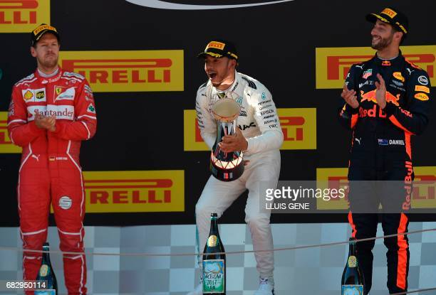 Ferrari's German driver Sebastian Vettel Mercedes' British driver Lewis Hamilton and Red Bull's Australian driver Daniel Ricciardo celebrate on the...