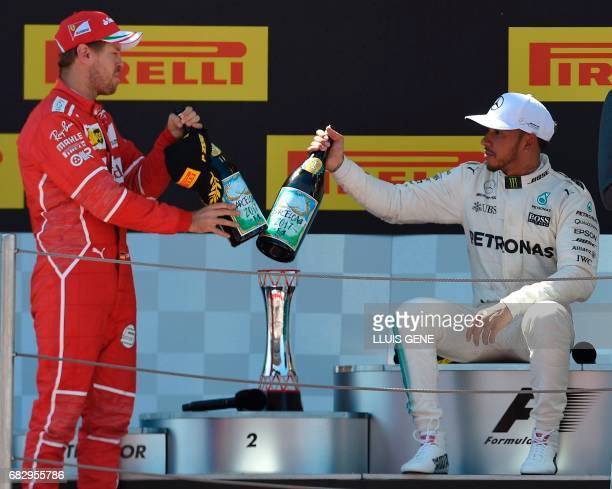Ferrari's German driver Sebastian Vettel Mercedes' British driver Lewis Hamilton celebrate on the podium after the Spanish Formula One Grand Prix on...