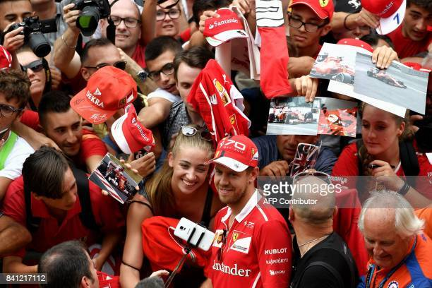 Ferrari's German driver Sebastian Vettel poses for pictures with supporters at the Autodromo Nazionale circuit in Monza on August 31 2017 ahead of...