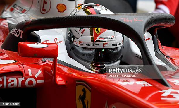 Ferrari's German driver Sebastian Vettel prepares to drive out of the pits during a practice session at Silverstone motor racing circuit in...