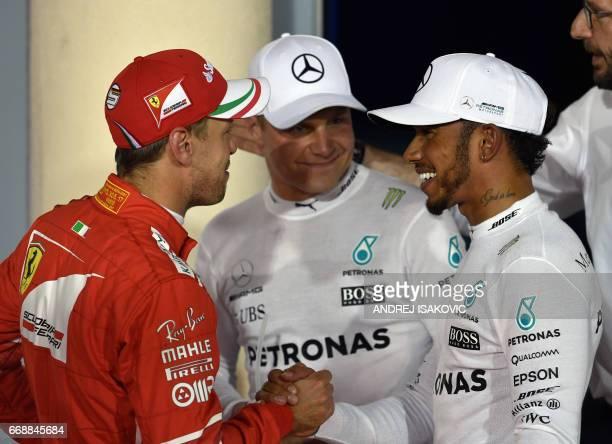 Ferrari's German driver Sebastian Vettel shakes hands with Mercedes' British driver Lewis Hamilton as Mercedes' Finnish driver Valtteri Bottas looks...