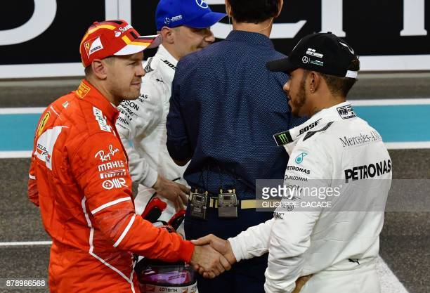 Ferrari's German driver Sebastian Vettel shakes hands with Mercedes' British driver Lewis Hamilton at the end of the qualifying session ahead of the...