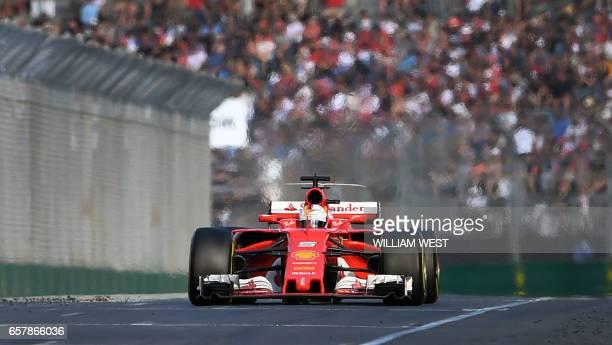 Ferrari's German driver Sebastian Vettel speeds down the main straight on the way to winning the Formula One Australian Grand Prix in Melbourne on...
