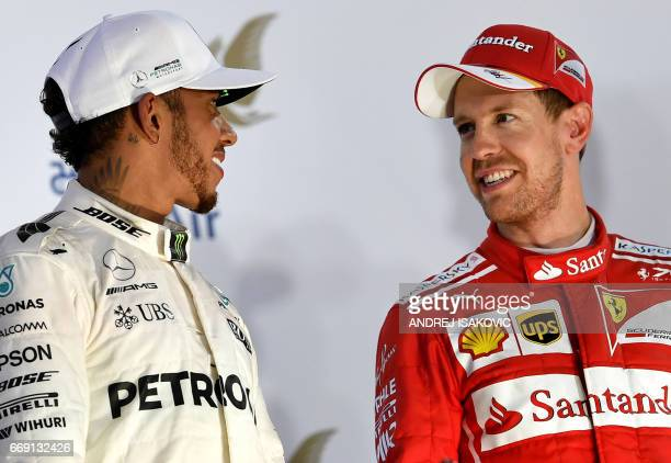 Ferrari's German driver Sebastian Vettel stands on the podium next to Mercedes' British driver Lewis Hamilton after winning the Bahrain Formula One...