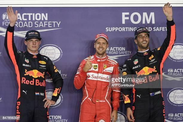 Ferrari's German driver Sebastian Vettel waves after securing pole position beside Red Bull's Dutch driver Max Verstappen and Red Bull's Australian...