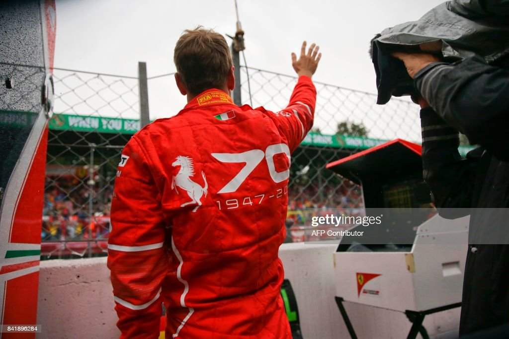 Ferrari's German driver Sebastian Vettel waves to supporters during a stop due to heavy rain during the qualifying session at the Autodromo Nazionale circuit in Monza on September 2, 2017 ahead of the Italian Formula One Grand Prix. / AFP PHOTO / POOL / Luca Bruno
