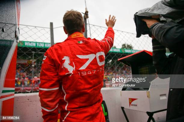 Ferrari's German driver Sebastian Vettel waves to supporters during a stop due to heavy rain during the qualifying session at the Autodromo Nazionale...