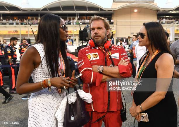 Ferrari's Gino Rosato flanked by British supermodel Naomi Campbell and Minttu Virtanen wife of Ferrari's Finnish driver Kimi Raikkonen stand on the...
