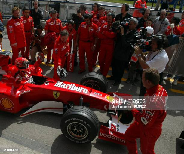 Ferrari's Michael Schumacher shrugs his shoulders in sympathy at Rubens Barrichello after pipping his teammate's lap time on the last lap to take...
