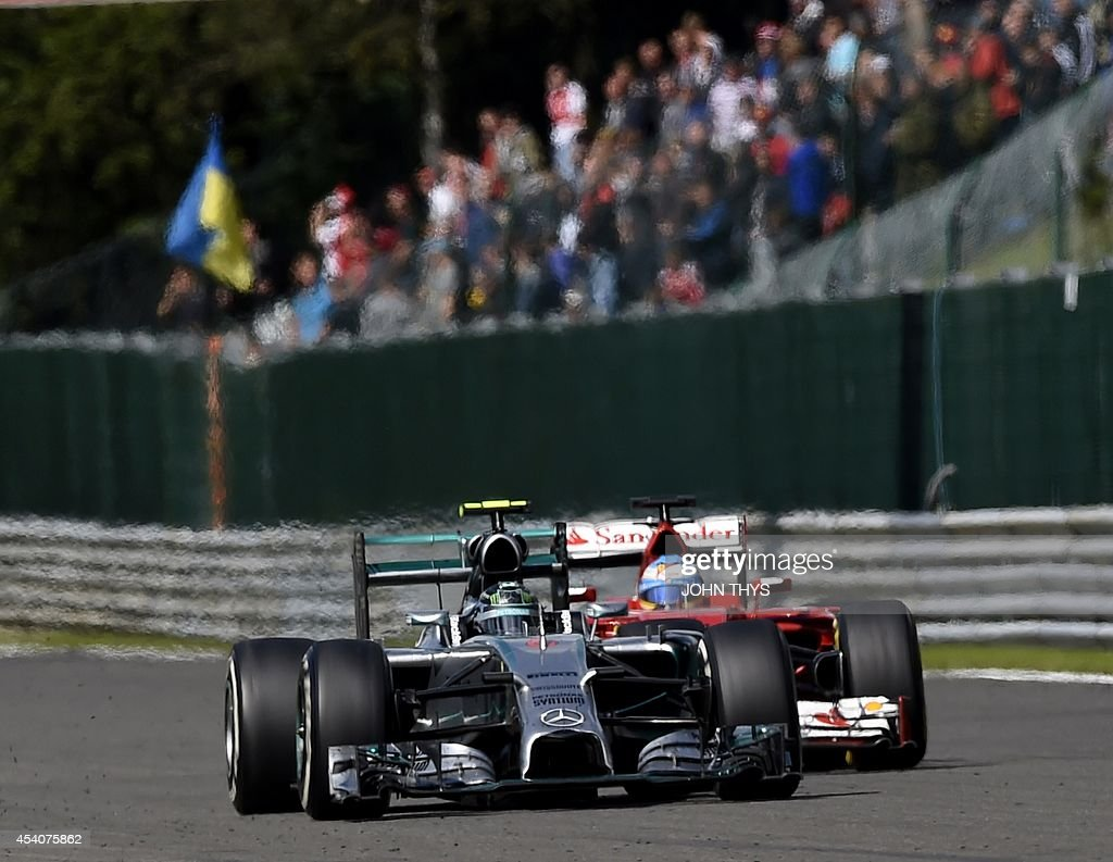 Ferrari's Spanish driver Fernando Alonso and Mercedes-AMG's German driver Nico Rosberg drive at the Spa-Francorchamps ciruit in Spa on August 24, 2014 during the Belgium Formula One Grand Prix. AFP PHOTO / JOHN THYS