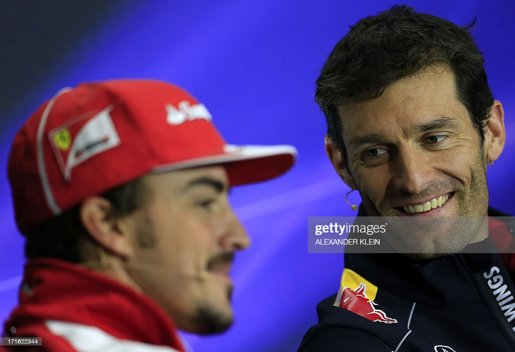 Ferrari's Spanish driver Fernando Alonso and Red Bull Racing's Australian driver Mark Webber speak during a press conference at the Silverstone...