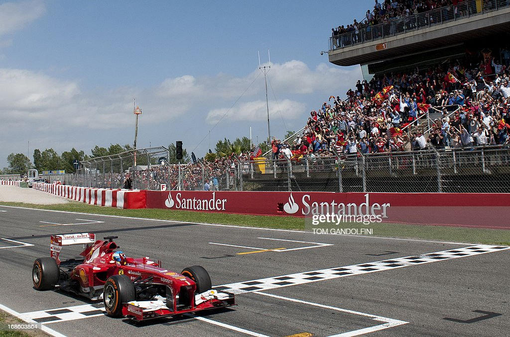 Ferrari's Spanish driver Fernando Alonso crosses the finish line at the Circuit de Catalunya in Montmelo near Barcelona on May 12, 2013 during the Spanish Formula One Grand Prix.