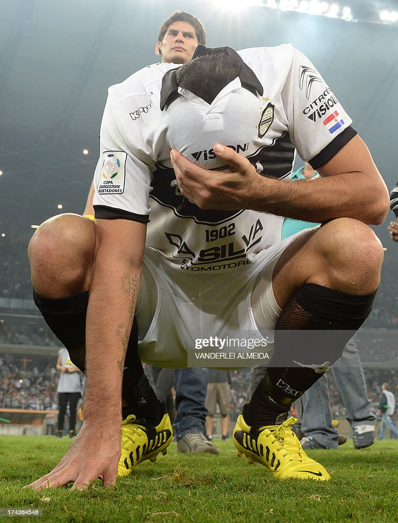 Ferreira of Paraguayan Olimpia (front) reacts after losing their Libertadores Cup second leg final football match shoot-out against Brazilian Atletico Mineiro at the Mineirao stadium in Belo Horizonte, Brazil on July 24, 2013. Atletico Mineiro won by 4-3 after a penalty shoot-out. AFP PHOTO / VANDERLEI ALMEIDA