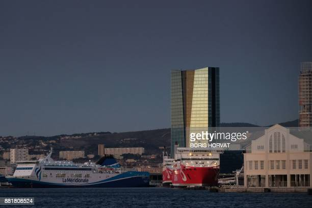 Ferries are docked on November 29 2017 in the port of Marseille near the CMACGM tower / AFP PHOTO / BORIS HORVAT