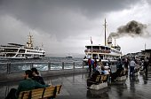 Ferries pass by in the distance as people sit on benches near the Bosphorus in Eminunu Istanbul on May 27 2015 AFP PHOTO / BULENT KILIC