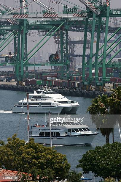 Ferries to Catalina Island pass cranes used to unload shipping containers in the Port of Los Angeles June 13 2007 in San Pedro California The US...
