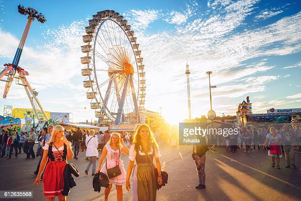Ferris Wheel and Visitors Walking Through Oktoberfest Fairgrounds, Munich, Germany