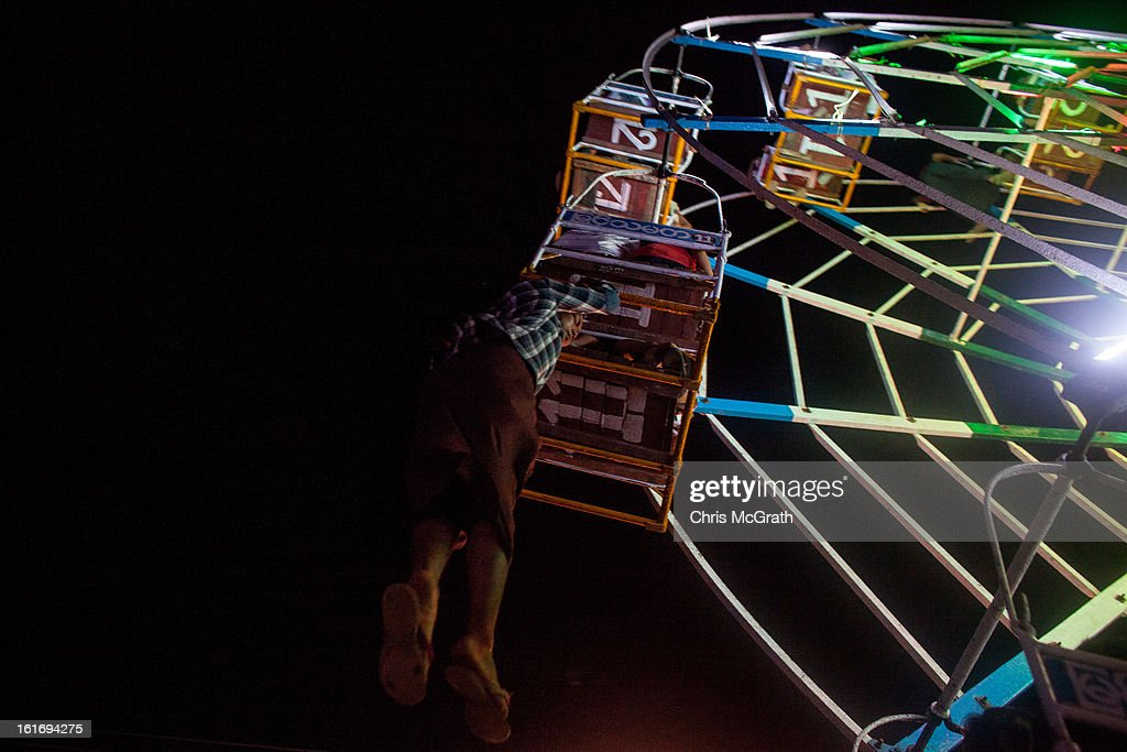 A ferris wheel attendant hangs from a cage to control the wheels spin on a man-powered ferris wheel attraction at a rural carnival in South Dagon Township on February 14, 2013 in Yangon, Burma. Myanmar is going through rapid political and economic reforms initiated by the countries first civilian president Thein Sein after years of military junta rule.