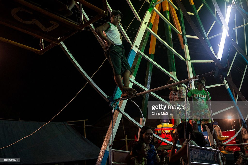 Ferris wheel attendants wait for customers before spinning the wheel at a rural carnival in South Dagon Township on February 14, 2013 in Yangon, Burma. The ferris wheel is man powered and takes seven men to spin it for their customers. Myanmar is going through rapid political and economic reforms initiated by the countries first civilian president Thein Sein after years of military junta rule.