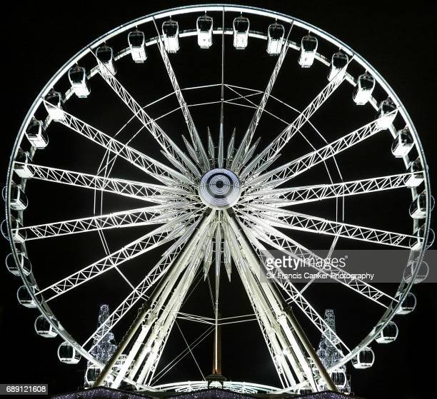 Ferris wheel illuminated at night, front view