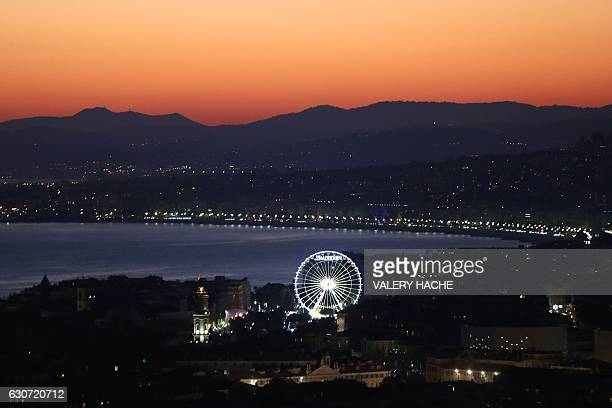 TOPSHOT A ferris wheel is illuminated as the sun sets over the French Riviera city of Nice southeastern France on December 31 2016 / AFP / VALERY...