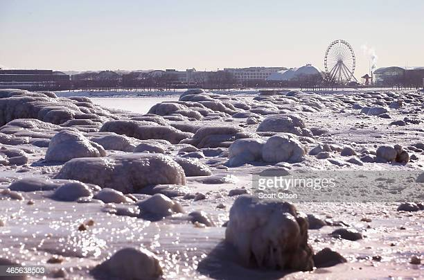 Ferris wheel on Navy Pier rises above ice along the shore of Lake Michigan on January 28 2014 in Chicago Illinois Temperatures in the city hovered...