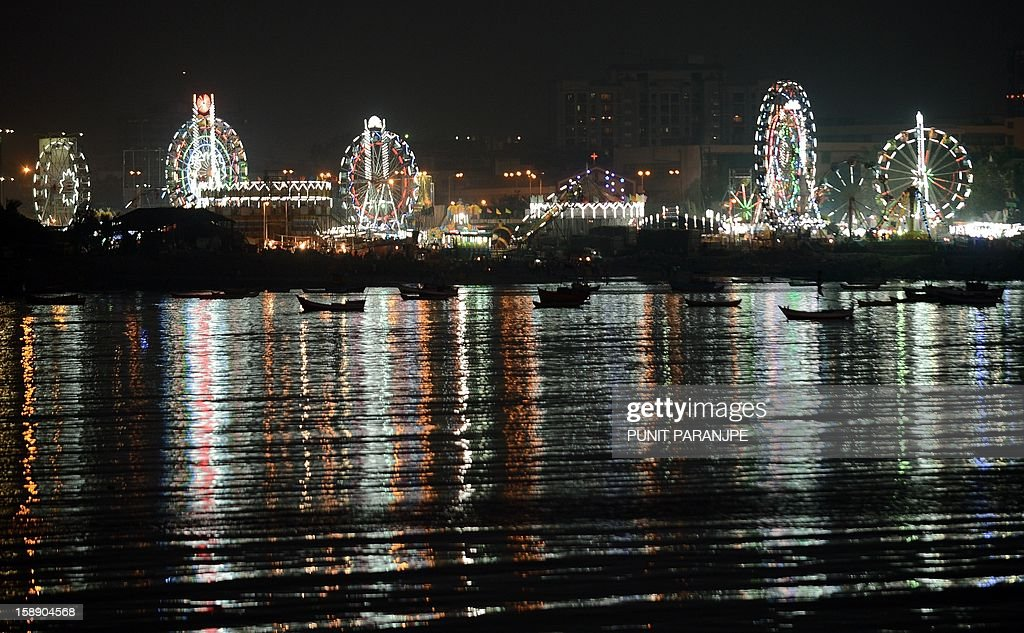 Ferris wheels are seen lit-up at night during an annual fair in Mumbai on January 3, 2013. The ten day-long fair is being held in honour of the Sufi saint Makhdoom Ali Mahimi on the dusty Mahim beach, which is full of people on giant wheels, toy trains and enjoying gravity-defying stunts in the 'Maut Ka Kuan' or 'Valley of Death'.