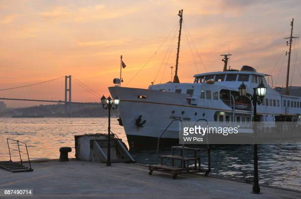 A ferry boat approaches the âengelk_y pier on the Asian shore of the Bosphorus The Bosphorus bridge can be seen in the distance