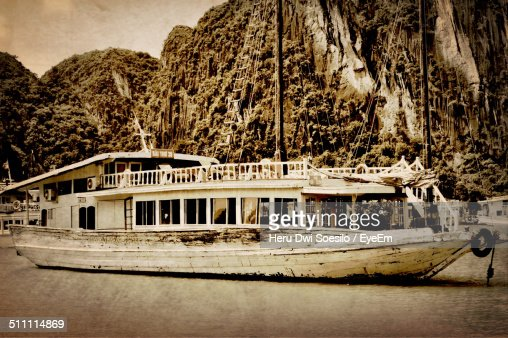 Ferry boat in river against mountains