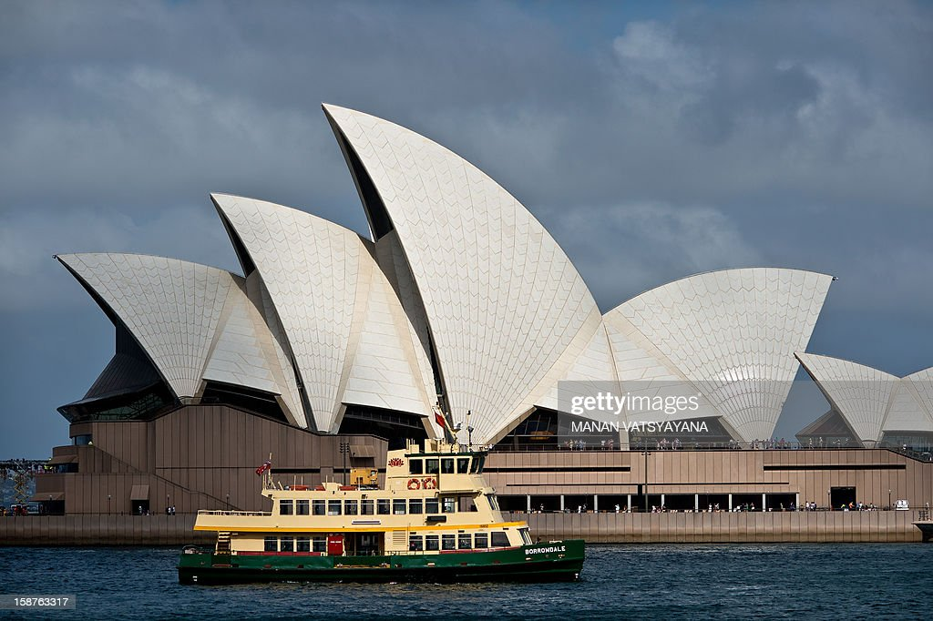 A ferry boat passes before the iconic Sydney Opera House in Sydney harbour on December 28, 2012. The world famous Australian centre for the performing arts is a venue for well known Australian and international performing artists including ballet, musical and theater.