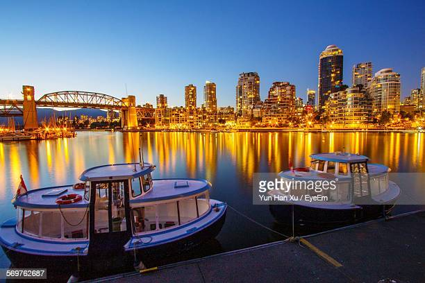 Ferry Boats Moored Against Illuminated Burrard Bridge In Granville Island