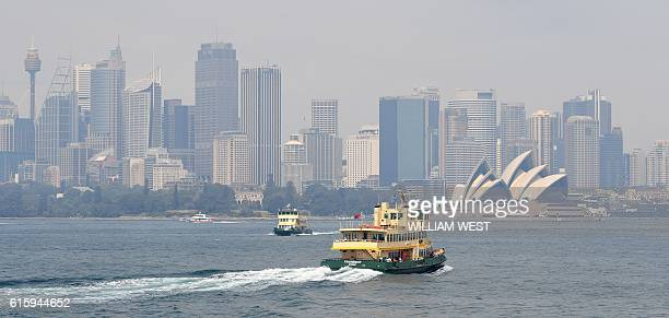 A ferry heads toward Sydney's Circular Quay as the city is shrouded in smoke on October 21 2016 The smoke drifted over the city from burnoffs on the...