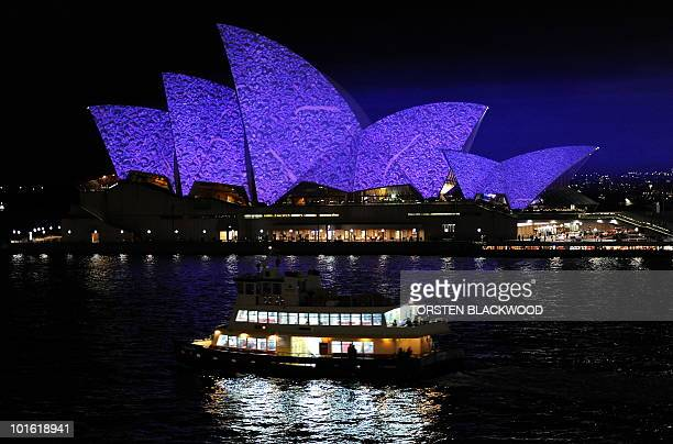 A ferry idles past as the Sydney Opera House sails are illuminated by American artist Laurie Anderson for the opening of VIVID Live across Sydney on...