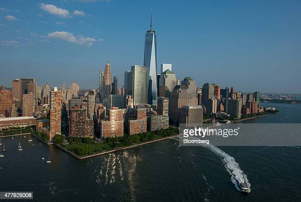 A ferry moves across the Hudson River as One World Trade Center stands in the Manhattan skyline in this aerial photograph taken above New York US on...