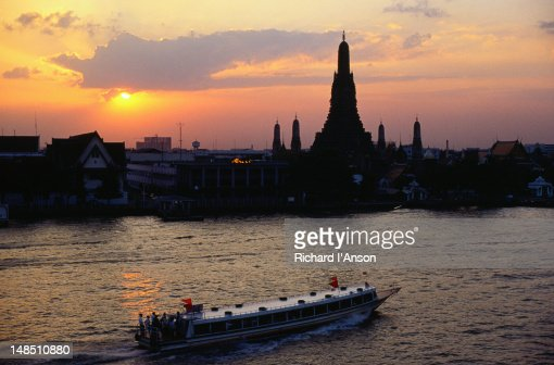Ferry on Chao Phraya (River) & Wat Arun silhouetted at sunset.