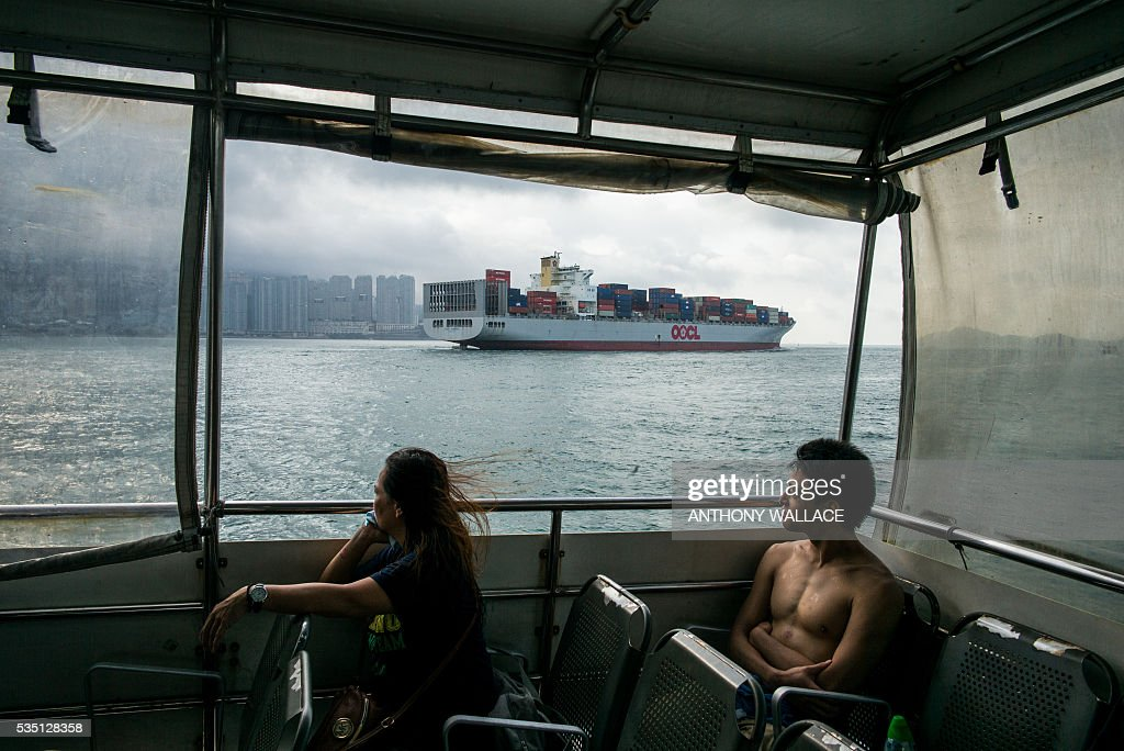 Ferry passengers look on as a cargo ship sails past during their commute between Lamma island and Hong Kong island (back L) early on May 29, 2016. / AFP / Anthony WALLACE