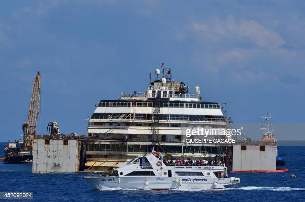 A ferry passes by the wrecked Costa Concordia cruise ship that lays off the Giglio island on July 13 2014 Italian authorities gave today their final...