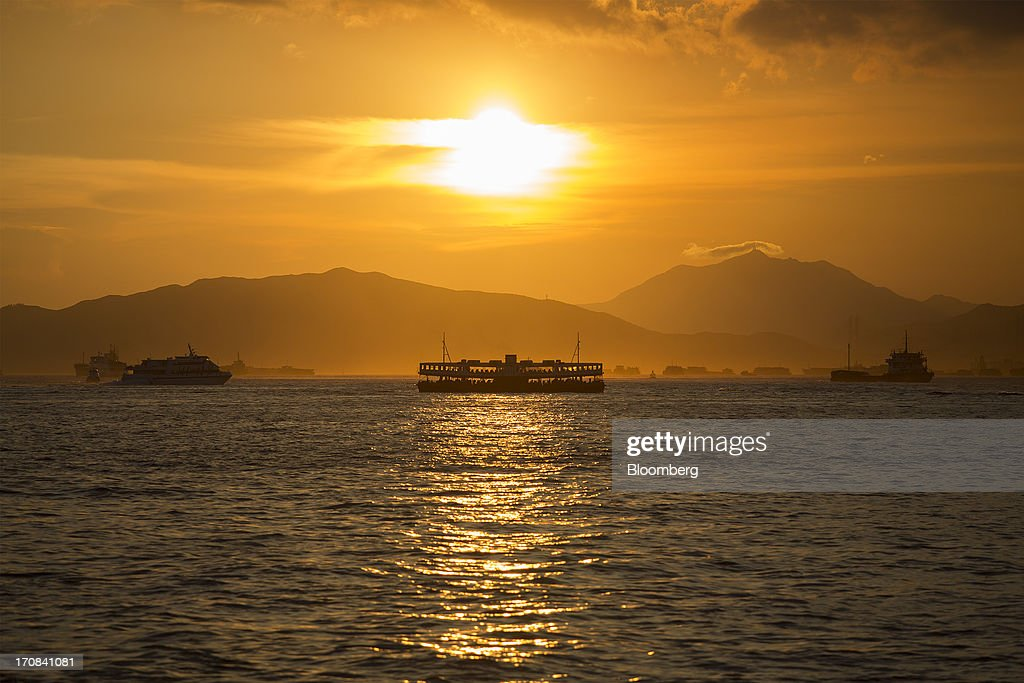 A ferry sails in Victoria Harbor as the sun sets in Hong Kong, China, on Tuesday, June 18, 2013. A shortage of housing, low mortgage costs and a buying spree by mainland Chinese have led home prices to more than double since the beginning of 2009, shrugging off repeated attempts by the government to curb gains amid an outcry over affordability. Photographer: Jerome Favre/Bloomberg via Getty Images