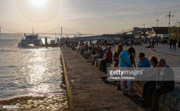 A ferry sails off while tourists and locals relax by the river in Cais do Sodre on October 31 2017 in Lisbon Portugal Although active all year round...