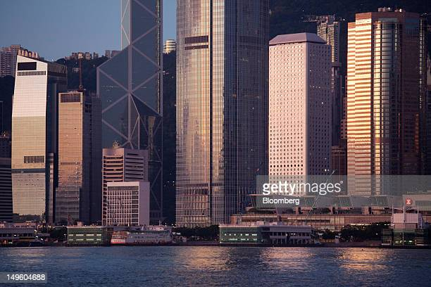 A ferry sits docked at a pier in front of Two International Finance Center center at sunrise in the central business district of Hong Kong China on...