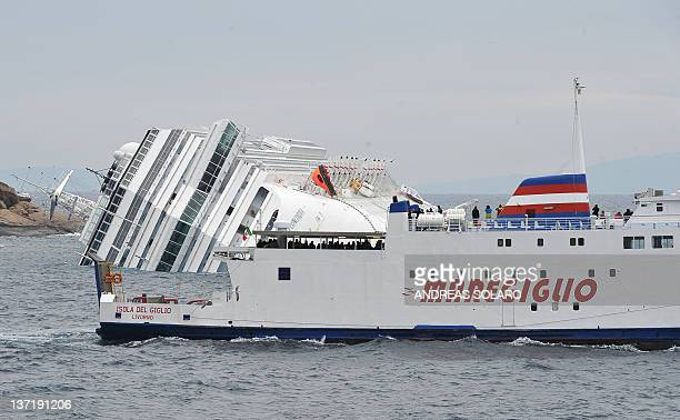 Ferryboat leaves the small harbour of the Tuscan island of Giglio on January 16 crossing the cruise liner Costa Concordia agrounded after hitting...