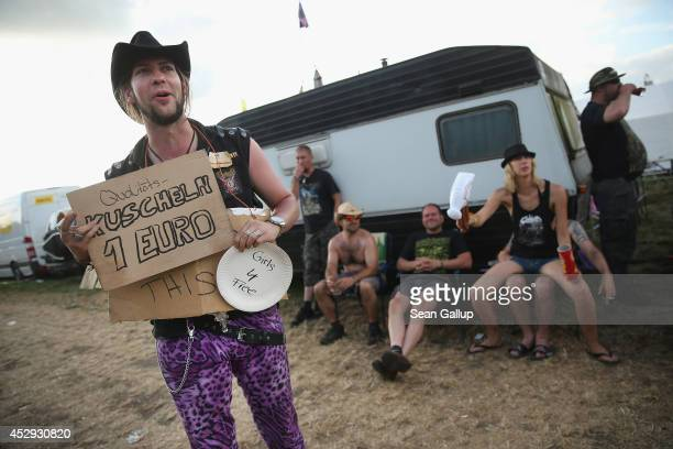 A fesitval goer holds a sign advertising 'quality hugging' for one Euro on the day prior to the first concerts at the 2014 Wacken Open Air heavy...