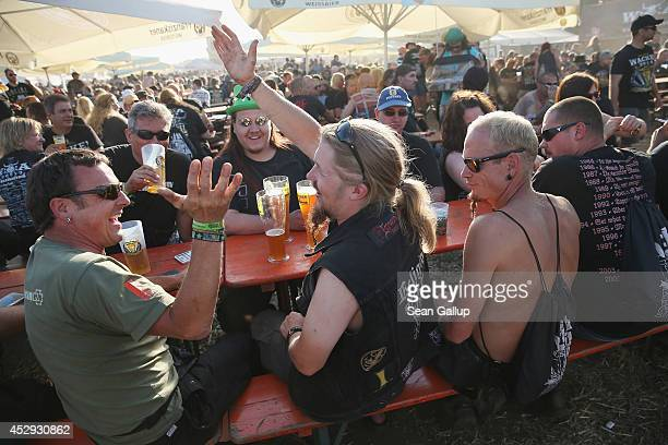 Fesitval goers sit at a beer garden on the day prior to the first concerts at the 2014 Wacken Open Air heavy metal music festival on July 30 2014 in...